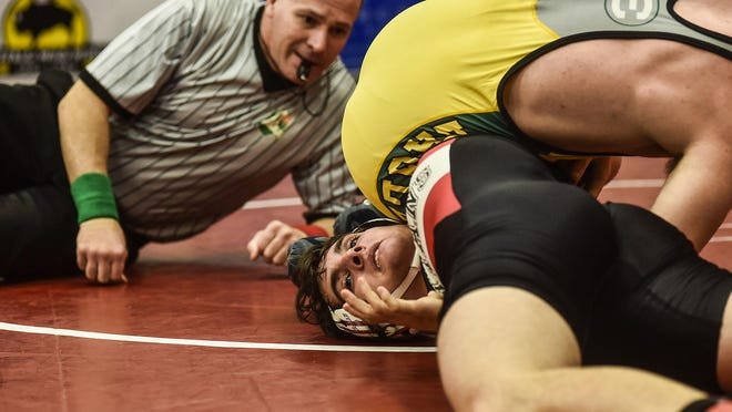 A referee keeps a close eye on the action as Pleasant's James Hood tries to get out of a lock while wrestling St. Edwards' Matt Henderson during the Harding Wrestling Invitational earlier this season. Hood and the Spartans will compete Wednesday in Oak Harbor for a Division III regional team championship.
