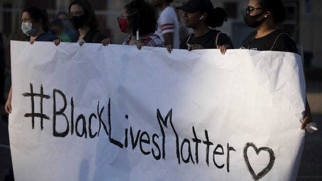 Jada Alfred, 36, right, and Tamara Harris, 30, to her left, both of whom grew up in Gahanna, help to hold a Black Lives Matter sign at the start of a march where around 500 people came out in support of Black Lives Matter, Thursday, June 11, 2020. The group marched from Friendship Park to Gahanna City Hall.