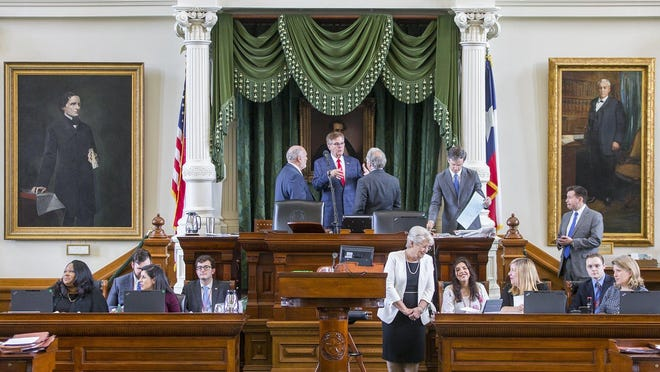 Paintings of Confederate President Jefferson Davis, left, and John H. Reagan, former postmaster general of the Confederacy, frame the presiding officer's desk in the Texas Senate.