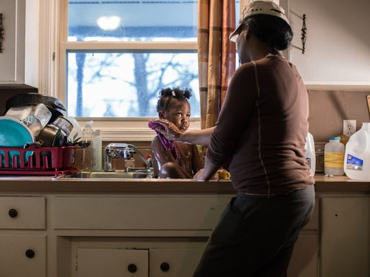 The 3-year-old girl in this photo, Marlana Bowen, has lived nearly her entire life without clean tap water, which means her mother, Ivory Gipson, 44, has to wash her in the sink of their home.
