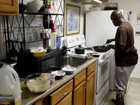Alonzo Scott makes food for a friend's birthday Thursday at his home in Redding. Scott has worked at many restaurants in and around San Francisco and learned many of his cooking techniques in the Episcopal Community Services of San Francisco's Chef's Program.