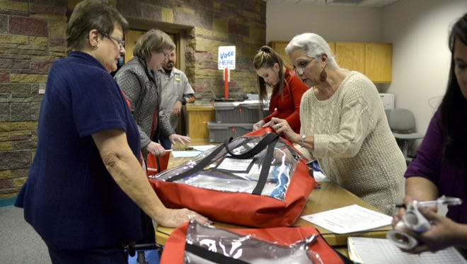 San Juan County Clerk's Office workers go through election bags with presiding judges Nov. 4, 2014, after the polls closed at the San Juan County Clerk's Office in Aztec.