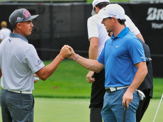Rickie Fowler, left, shakes hands with Rory McIlroy of Northern Ireland, on the 18th green during practice at the World Golf Championships Bridgestone Invitational, Tuesday, July 29, 2014, in Akron, Ohio. (AP Photo/Phil Long)