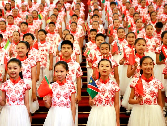 Chinese children hold flags during a rehearsal prior