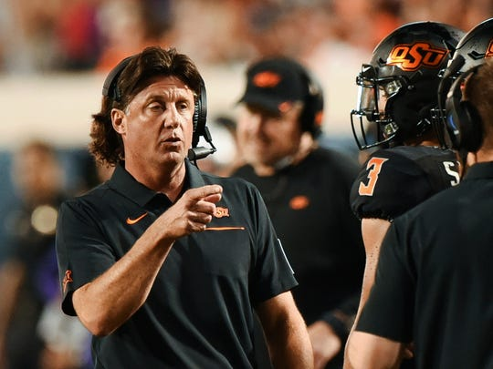 Oklahoma State head coach Mike Gundy points to his staff on the sidelines during the first half of an NCAA college football game against Kansas State, in Stillwater, Okla., Saturday, Sept. 28, 2019. (AP Photo/Brody Schmidt)
