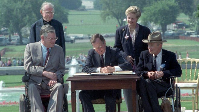 President George H.W. Bush signs the American With Disabilities Act on the South Lawn of the White House on July 26, 1990. With him are (seated from left) Evan Kemp, chairman of the Equal Employment Opportunity Commission, Justin Dart, chairman of the President's Committee on Employment of People with Disabilities and (standing) the Rev. Harold H. Wilke, who was born without hands, and Swift Parrino, mother of a child with a disability and chairman of the National Council on Disability.