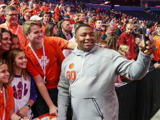 Clemson defensive lineman Dexter Lawrence, right, gets a selfie with the phone of Jefferson Summers, middle, of Greenville while fans watch media day on Saturday, during college football national championship week in Tampa, Florida.