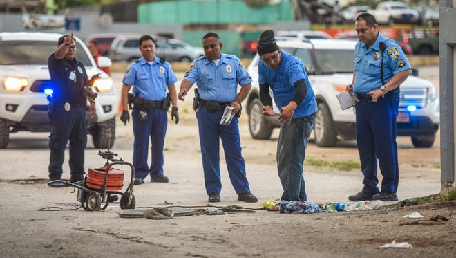 Inland Builders Corp. plumber Johnny Teopaco, second from right, explains to Guam Police Department officers how he found and helped his co-worker who had been injured in an auto-pedestrian incident at the old Hafa Adai Exchange in Tamuning on Tuesday, Jan. 17, 2017. Teopaco said he had momentarily stepped away from the manhole and upon his return, found his co-worker seriously injured while partially remaining in a manhole.