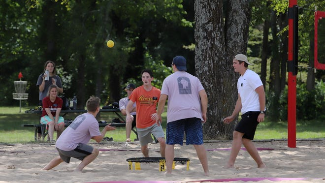 Friends gather for a game of Spike Ball at Ben Geren Regional Park, Monday, July 27, 2020, after setting their pitch on half of a sand volleyball court in the shade.