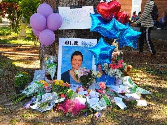 A  memorial has been set up under a large oak tree in the courtyard of Rockledge High School for beloved Rockledge High teacher of the year Sandra Cook. Students gathered by the tree during their lunch hour, adding flowers, notes, artwork  and balloons to the  memorial.