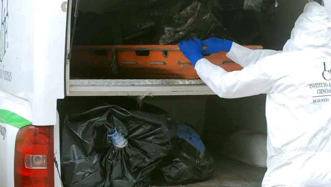 A forensic expert removes corpses in body bags from mass graves in La Barca, Jalisco, Mexico.