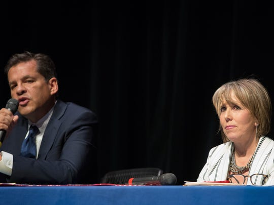 Michelle Lujan -Grisham, right, looks off stage as