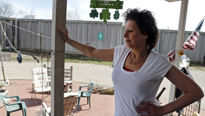 Sara Huolihan of Fox Crossing stands on her back porch as she describes the issues she has faced because of the State 441/U.S. 10 expansion project.