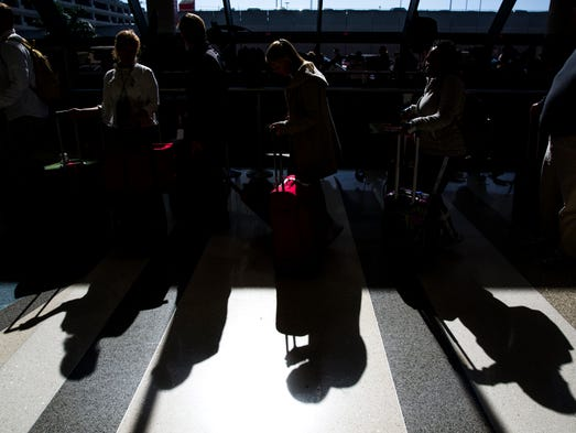 Delta passengers wait in a line that wraps outside