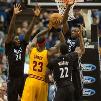 Jan 31, 2015; Minneapolis, MN, USA; Cleveland Cavaliers forward LeBron James (23) attempts to shoot over Minnesota Timberwolves guard Andrew Wiggins (22), forward Anthony Bennett (24) and center Gorgui Dieng (5) during the fourth quarter at Target Center. The Cavaliers defeated the Timberwolves 106-90. Mandatory Credit: Brace Hemmelgarn-USA TODAY Sports