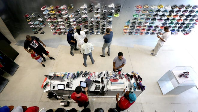 Customers checks out sneakers at Nojo Kicks a new urban high-end sneaker, jersey and hat retailer on Library Street in downtown Detroit, Wednesday, June 25, 2014.