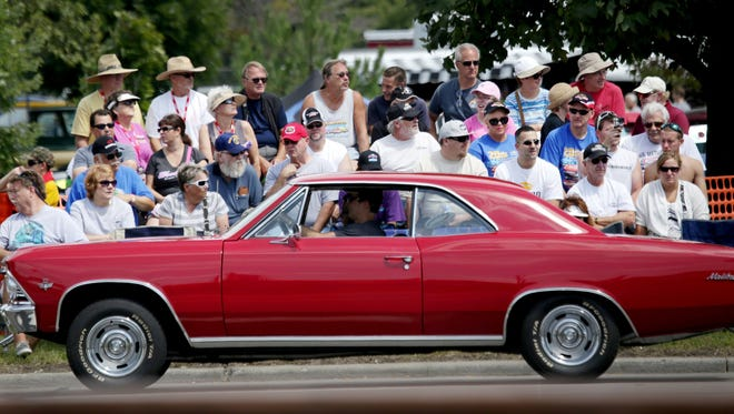 Car enthusiasts watch classic cars pass by from bleachers during the 2014 Woodward Dream Cruise along Woodward Avenue on Saturday, Aug. 16, 2014.