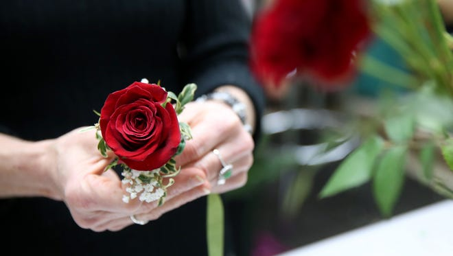 Susan Brown, a floral designer, create a red rose corsage a few hours before SnoBall at Lollypops and Roses flower shop in Salem on Saturday, Dec. 2, 2017.
