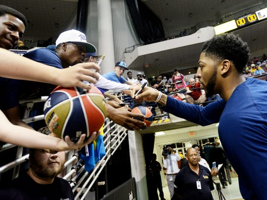 Anthony Davis of the New Orleans Pelicans stops to sign an autograph during their game against the Dallas Mavericks Saturday evening at CenturyLink.