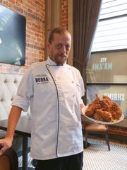 Jammie Monaghan, the executive chef at Bubba in Des Moines, poses with a plate of fried chicken.
