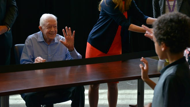 Former President Jimmy Carter waves during a book signing at the downtown branch of the Nashville Public Library on Wednesday.