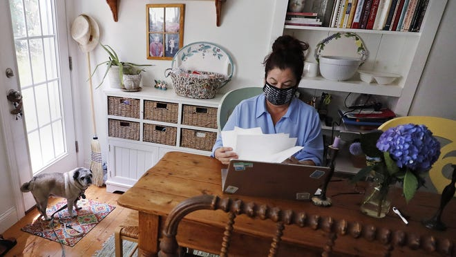 """Poet Tammi Truax looks over her recent work, as her pug """"Pie"""" looks on, while seated at her writing table, wearing a protective mask due to the COVID-19 virus outbreak July 29 at her home in Eliot, Maine."""