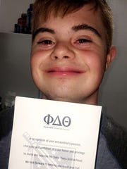 Arik Ancelin shows bid card he received to become honorary member of Phi Delta Theta fraternity at Florida State University on Oct. 14, 2017.