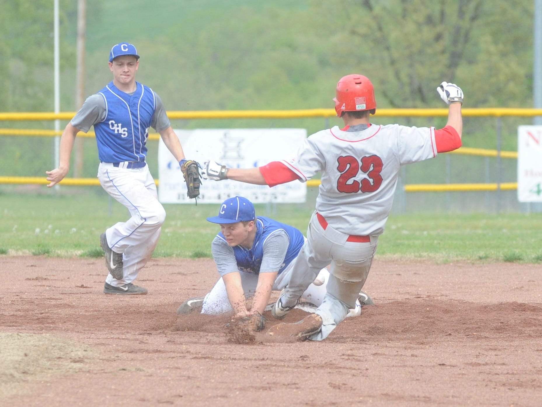 Cotter second baseman Maddux Adams, middle, takes a throw on a steal attempt by Flippin's Dean Smyser, right, while shortstop Shawn White backs up the throw during the Bobcats' 2-1 victory over the Warriors earlier this season at Cotter. The two teams meet Monday in the district final at Harrison.