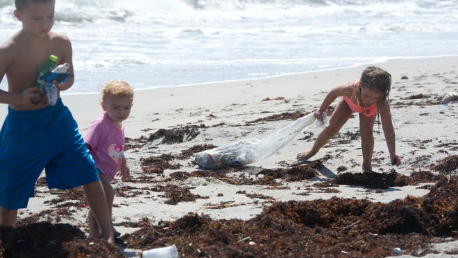 """Siblings (from left) Spencer McKown, 7, Marli McKown, 1, and Lena McKown, 4, of Port St. Lucie, pick up trash Monday, August 31, 2015, at Hobe Sound Beach. """"I've never seen so much trash on the beach before,"""" said their mother, Christina McKown. The family found a plastic bag on the beach and they were motivated to fill it with trash as they walked the coast. """"Normally this beach is very clean,"""" said EMT/Ocean Lifeguard Joe Ryan."""
