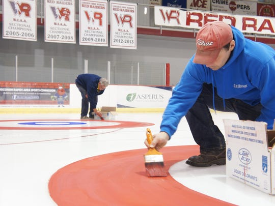 Jim Arnold, right, and Mike Swanson paint the circles for the curling sheet for this weekend's Marsh Madness Summer Bonspiel at the SWC Recreation Center.