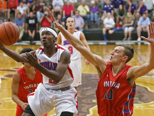From left, Eugene German (3), of Gary 21st Century, takes a shot despite defense from junior Jack Nunge (40), of Castle, during the Indiana boys junior All-Stars versus senior All-Stars, at Bloomington South, June 7, 2016.