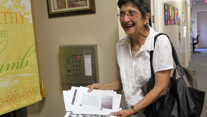 Retired teacher Carol Pannell holds a yearbook page of her former fourth-grade class at Trinity Catholic School in Tallahassee, Fla., and a printout of Samuel Fernandez Dominguez's message after he found a bottle with a note the class sent back in 1998.