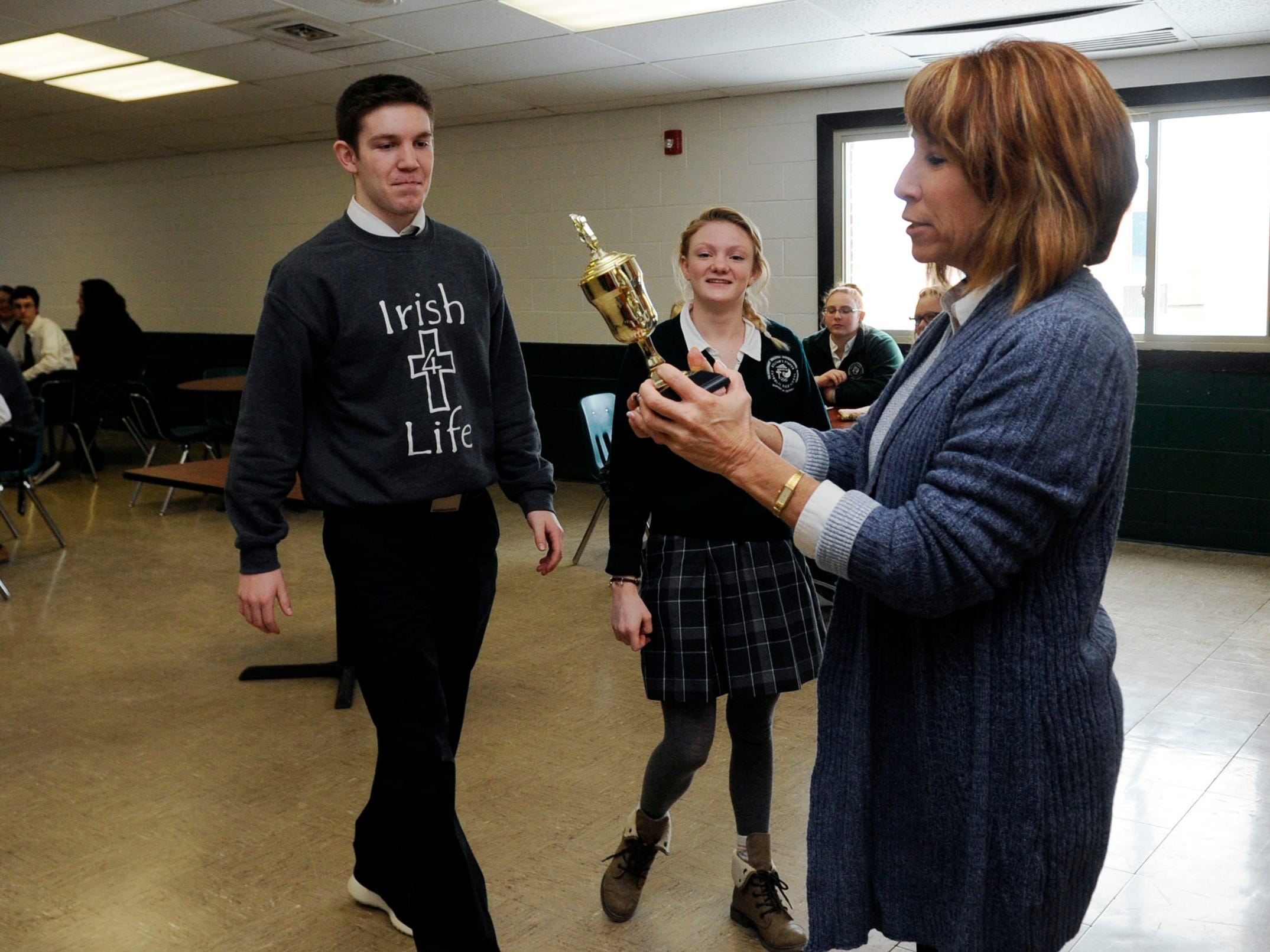 """Fisher Catholic principal Maureen """"Mo"""" Beck presents the 2015 Lancaster Eagle-Gazette Battle of the Fans Champion trophy to Eli Frazier, left, and Adriana DeGenova, center, Wednesday at Fisher Catholic High School in Lancaster."""