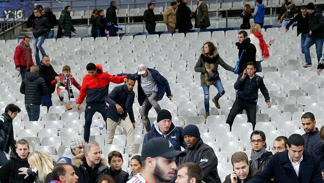 Soccer fans head to the field at the Stade de France stadium after an international friendly soccer match in Saint Denis, outside Paris, Friday, Nov. 13, 2015. An explosion occurred outside the stadium. Several dozen people were killed in a series of unprecedented attacks around Paris on Friday.