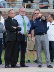 Notre Dame coach Brian Kelly, right, chats with university president Rev. John Jenkins, left, and athletic director Jack Swarbrick.