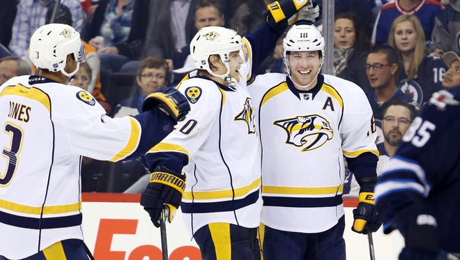 Predators forward James Neal, right, celebrates his third-period goal against the Jets with teammates.