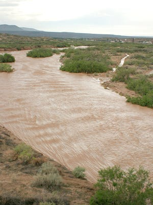 The Rio Grande flows rapidly near Hatch, N.M. after the heavy rainstorms flooded much of the area forcing Hatch residents to take shelter at Hatch Valley High School, on Aug.15, 2006.