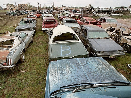 - Rows of vehicles damaged by the tornado fill an empty lot on the edge of Spencer.