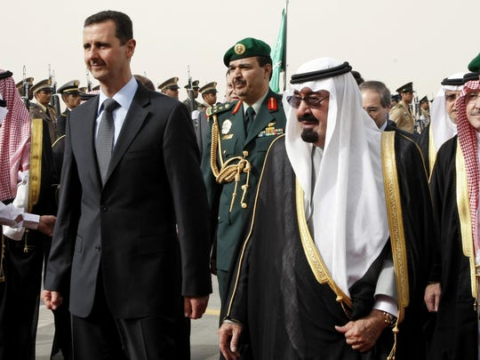 In this March 11, 2009 file photo, King Abdullah of Saudi Arabia, right, welcomes Syrian President Bashar Assad upon his arrival to attend the Arab Summit, in the Saudi capital Riyadh.