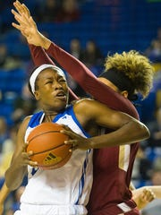 The University of Delaware's Nicole Enabosi, 33, uses her elbow to push past the College of Charleston defense Sunday at the Bob Carpenter Center.