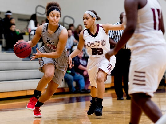 West's Madi McCoy (12) dribbles past Fulton's Reigny Tory (22) during a game between Fulton and West high schools at Fulton in Knoxville, Tennessee on Friday, Dec. 22, 2017.