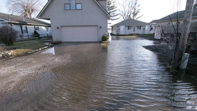 The roadside and side yards of a Branch Drive home in the 8000 block in Hamburg Township are flooded Tuesday, Feb. 27, 2018.
