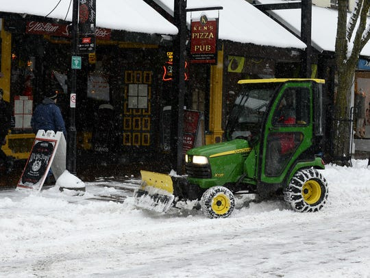 A plow clears snow from the Church Street Marketplace