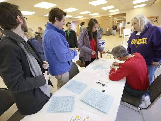 New voters register before casting their ballots at the First United Methodist Church polling station  Tuesday in Appleton.
