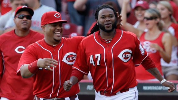 Cincinnati Reds starting pitcher Johnny Cueto (47) runs onto the field with Brayan Pena after the Reds defeated the Pittsburgh Pirates 4-1 to give Cueto his 20th win.