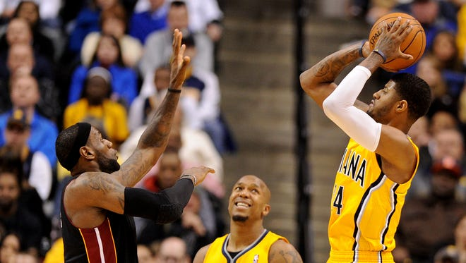 Indiana Pacers forward Paul George takes a jump shot over Miami Heat forward LeBron James as forward David West looks on inside Bankers Life Fieldhouse, Wednesday, March 26, 2014, in Indianapolis. The Pacers won the game 84-83.