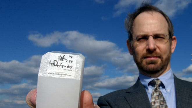 In this Oct. 23, 2003, file photo, Ira Goldman is shown with his invention, the Knee Defender, at Washington's Reagan National Airport. Goldman invented the device, a beeper-sized block of plastic that lets airline passengers prevent the seat in front of them from reclining. At the time, aviation officials worried about the disagreements that would be generated at 30,000 feet. They were banned by most airlines.