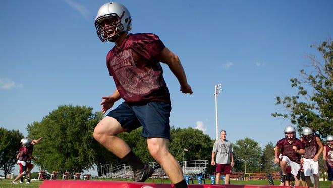 Jake Rueth runs through footwork drills during football practice at Loyal High School.