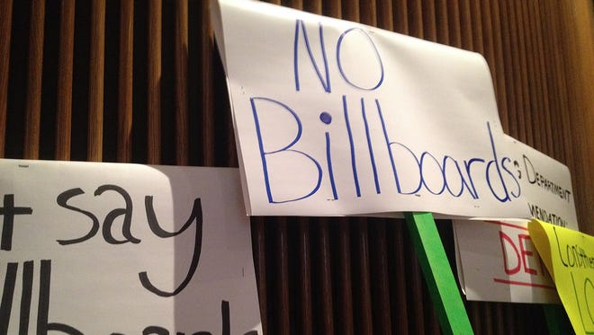 Signs made by Glendale and Peoria residents rest along the back wall of City Council chambers March 19, 2014.
