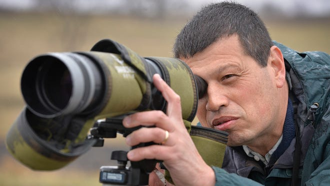 St. John's University biology professor Philip Chu uses a spotting scope, set lower to accommodate visitors, to observe waterfowl on a 40-acre settling pond late last month just south of Albany.